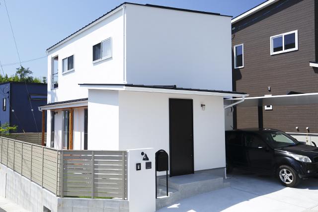 真っ白な塗り壁に黒の玄関周りでシャープな外観
