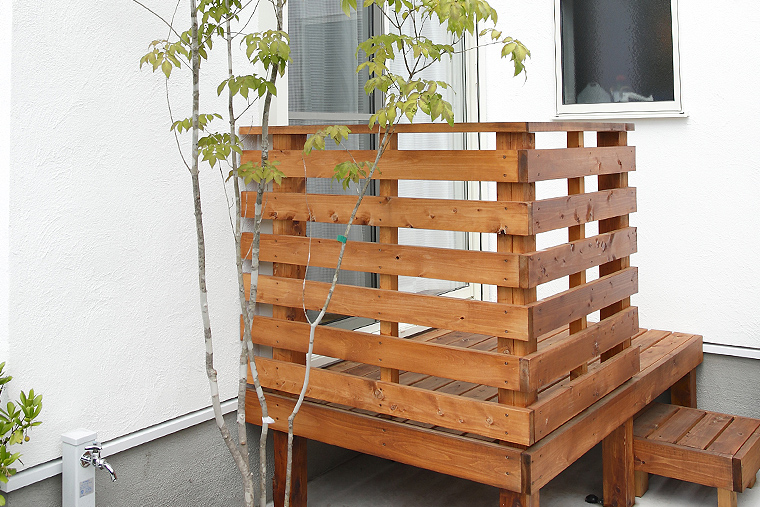 外壁に映える植木とコンパクトな木製デッキ
