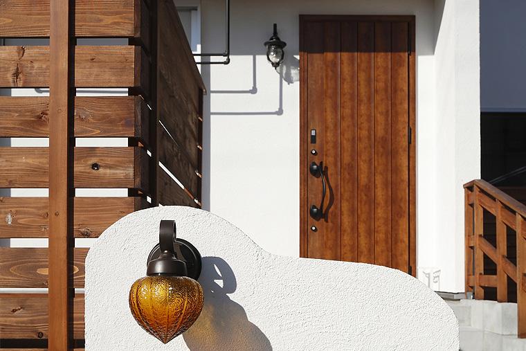 白い塗り壁に映える玄関ドア